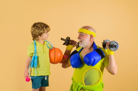 Family sport. Grandfather and kid sporting. Family time together. Portrait of healthy grandfather and son workout. Boxing gloves. Dumbbells. Sporting. Basketball