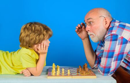 Checkmate. Child boy playing chess with grandfather. Games and activities for children. Grandfather and grandson playing chess. Little boy think or plan chess game. Little boy learning to play chess