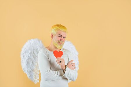 Cupid holds valentine's heart. Handsome angel Cupid. Love concept. Valentine angel. Bearded man with angel wings.