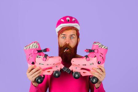 Man with roller skates and helmet. Active sport. Roller skating ride. Healthy lifestyle. Bearded man with roller-skates. Holidays. Vacation. Protective sport helmet. Protective sport equipment.