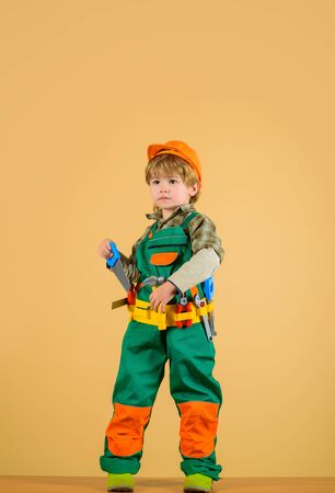Little kid repairman holds saw in hand. Work with tools. Repair. Little boy in builder uniform with tools belt. Builder boy in helmet and toolbelt. Serious toddler with tools for building. Child game