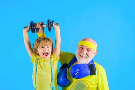 Grandfather and kid sporting. Family time together. Family sport. Portrait of a healthy grandfather and son work out with dumbbells . Boxing gloves. Dumbbells. Sporting Foto de archivo - 139728439