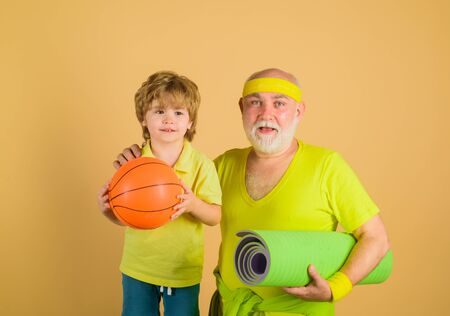Family time. Grandfather and kid sporting. Family sport. Thumbs up. Old man with yaga carpet. Portrait of healthy grandfather and son workout. Basketball. Yoga. Sporting. Sport game