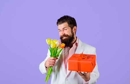 Smiling man hold valentines present and flowers. Valentines Day. Present box.