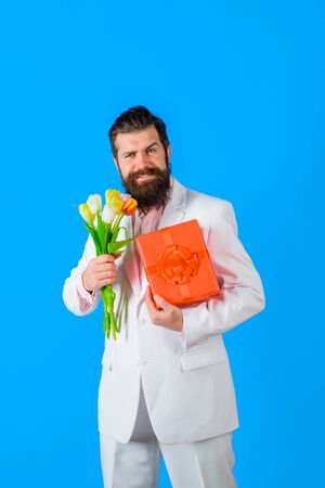 Smiling man holds valentines present and flowers. Present box. Bouquet of flowers. Happy Valentine's Day. February 14. Stock fotó