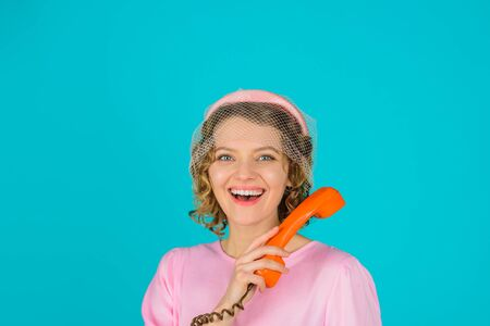 Woman talking on retro phone. Smiling woman in pink dress with telephone handset. Happy woman holds handset. Pretty woman talking at retro handset. Girl talking on landline phone. Communication