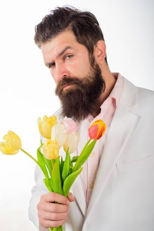 Businessman with bouquet of tulips for birthday. Romantic. Bearded man holds bouquet of flowers. Valentines Day. Womens Day. Serious man holds flowers. Bouquet of tulips. Handsome man with flowers