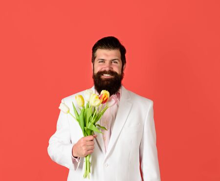 Bouquet of tulips. Handsome man with flowers. Businessman with bouquet of tulips for birthday. Romantic. Bearded man holds bouquet of flowers. Valentines Day. Womens Day. Serious man holds flowers