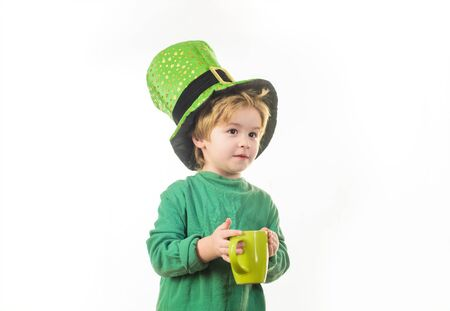 Green leprechaun. Child in green hat holds cup. Green hat with clover. Saint Patrick's Day. Traditions of Saint Patrick Day. St Patrick's Day. Green top hat. Leprechaun. Sale. Discount. Advertising