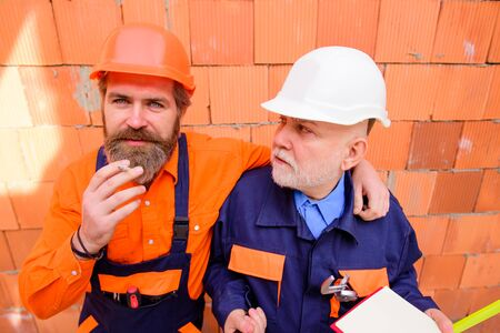 Foreman in safety helmet and overalls smoking cigarette. Builder man construction worker smoking cigarette. Portrait of handsome bearded engineer relax by smoking during break in construction site Imagens