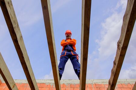 Roofer carpenter builder working on roof structure on construction site. Construction worker on construction site. Professional builder worker in protective helmet at house building construction site