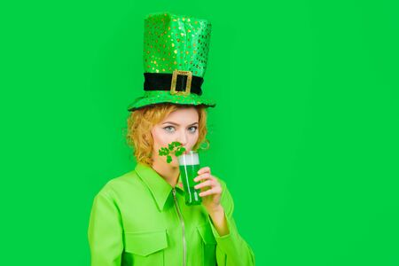 Green beverage with clover. Irish Traditions. St Patricks Day. Woman drink beer. Spring festival. Girl in green leprechaun hat drinking green beer. St Patricks Day celebration. Patrick Day pub party
