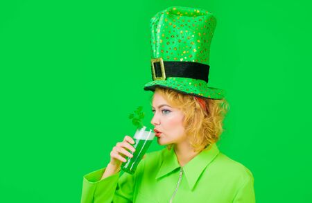 St Patrick's Day celebration. Beautiful woman in green hat with beer. Shamrock leaf in beer. Leprechaun girl drinks green beer pint. Young girl in saint patrick day.Celebrating Patricks Day pub party Zdjęcie Seryjne - 143014707