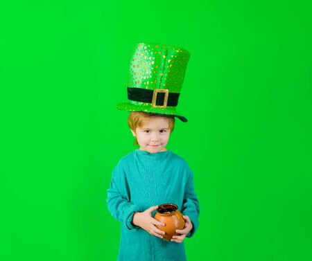 Patricks Day. Green top hat. Boy in green hat holds pot with gold. Leprechaun. Green leprechaun. Green hat with clover. Saint Patricks Day. Traditions of Saint Patrick Day. Sale. Discount. March