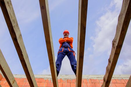 Construction worker on construction site. Roofer carpenter builder working on roof structure on construction site. Professional builder worker in protective helmet at house building construction site