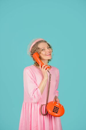Smiling woman talking by retro phone. Girl holds handset. Landline phone. Communication. Woman in pink dress with telephone handset. Phone communication