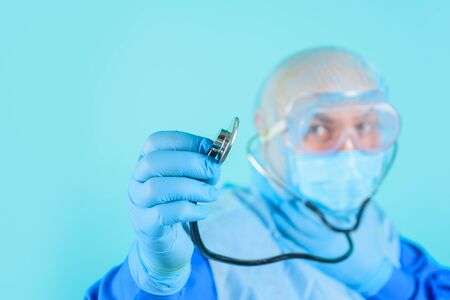 Doctor in protective suit and medical mask. Healthcare and medicine concept. Doctor with stethoscope in hand. Selective focus. Diagnostic instrument, hospital equipment. Advertising hospital, clinic Standard-Bild