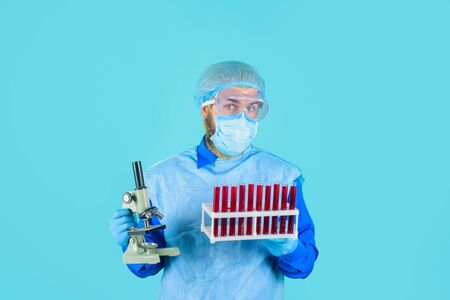 Laboratory work. Man in medical mask and glasses hold test tubes. Doctor in protective suit and mask with test tubes and microscope. Technician holds rack with blood test tubes in research laboratory Standard-Bild