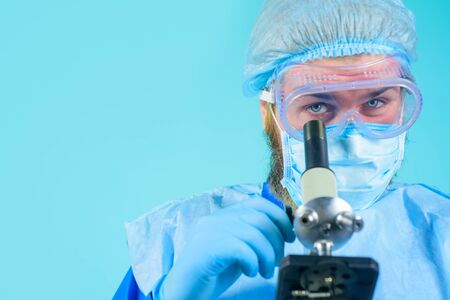 Male medical doctor using microscope in laboratory. Scientist with microscope making test or research in clinical laboratory. Doctor in protective mask and gloves examining sample through microscope.