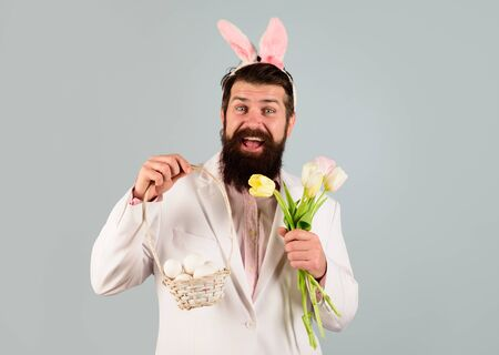 Happy Easter. Preparation for Easter. Rabbit man in bunny ears with flower. Bearded man in suit holds basket with eggs. Spring holiday. Spring flower. Easter bunny costume. Easter celebration concept Standard-Bild