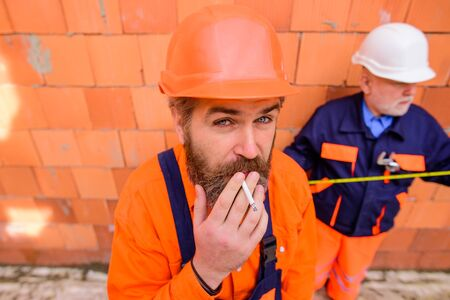 Builder man construction worker smoking cigarette. Portrait of handsome bearded engineer relax by smoking during break in construction site. Foreman in safety helmet and overalls smoking cigarette
