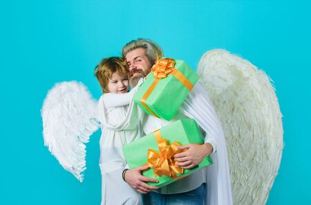 Happy father in angel costume with little son angel holds present. Cute angel. Valentines day. Father and son Angels. Father's day. Little cupid boy gives father gift. Christmas angels. Gift box Standard-Bild