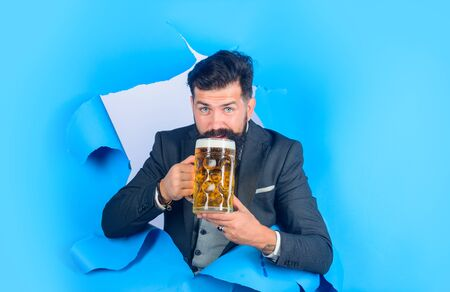 Bearded man holds craft beer looking through paper hole. Drinks, alcohol, leisure, people concept. Satisfed man with beard holds mug of beer. Stylish man drinks beer. Lager and dark beer. Oktoberfest