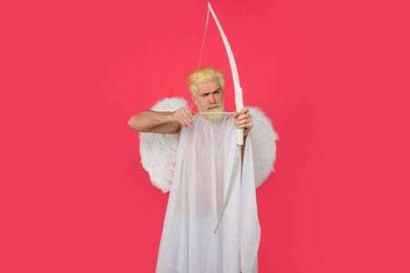 God of love. Cupid. Amour. Cupid with bow. February 14. Cupid angel with bow and arrows. Symbol of love. Happy Valentines Day. Serious man in angel costume. Valentines day angel. Cupid shoot with bow