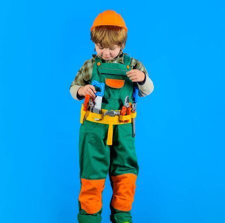 Builder boy in helmet and toolbelt. Little kid repairman holds saw in hand. Smiling toddler with tools for building. Child game. Work with tools. Repair. Little boy in builder uniform with tools belt