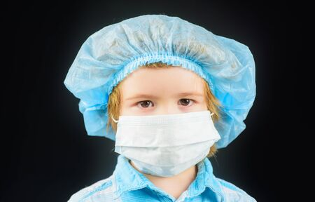 Concept of coronavirus quarantine or covid-19. Protection against coronavirus. Small boy with mask on face. Toddler in medical mask. Virus and infection control concept. Illness prevention. Closeup Standard-Bild
