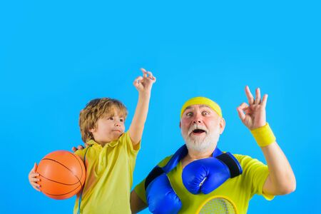 Family time. Grandfather and grandson shows sign ok. Family sport. Old man with boxing gloves. Boy holds basketball ball. Grandfather and son workout. Boxing gloves. Sporting. Basketball. Sport game