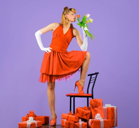 Woman in red dress with retro hairstyle. Happy Valentine's Day. Flowers and gift. Happy girl with gift and bouquet of tulips. Present box. Bouquet of tulips. Retro woman with present box and flowers