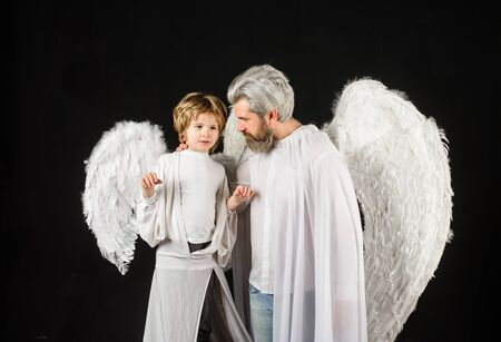 Cute angel. Gorgeous kid. Valentines day. Father and son Angels. Father's day. Little cupid boy and father in white clothes. Happy father in angel costume with little son angel. Christmas angels Standard-Bild