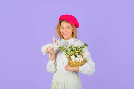 Happy Easter day. Girl in fashionable beret hold basket with eggs and small bunny. Easter egg. Tradition of Easter. Basket with eggs. Easter bunny rabbit. Beret hat. Accessory for woman. French style Standard-Bild