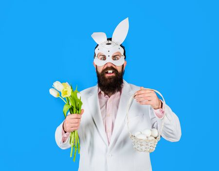 Happy bearded man with bunny ears hold basket with eggs. Man with bouquet tulips. Bunny man. Easter hunt. Bunny ears. Spring sale. Discount. Preparation for Easter. Easter Day. Happy easter. Holidays Standard-Bild
