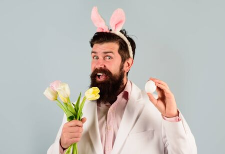 Happy Easter. Bearded man. Eggs hunt. Rabbit costume. Religion symbol. Preparing for Easter. Easter eggs. Spring holidays. Easter celebration concept. Smiling bearded man in suit hold egg and flowers