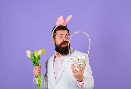 Rabbit man in bunny ears with flower. Bearded man in suit holds basket with eggs. Happy Easter. Preparation for Easter. Spring holiday. Spring flower. Easter bunny costume. Easter celebration concept