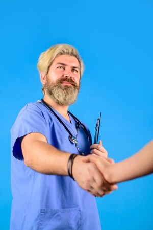 Smiling doctor shaking hands with patient in clinic. Male medicine practitioner and patient handshake in office. Partnership, trust, medical ethics concept. Medical doctor shaking hands with patient