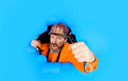 Worker in protective helmet breaking paper. Builder holds wrenches. Repairment tools. Spanner. Bearded builder man with wrenches looking through paper. Man builder with wrenches looking through paper