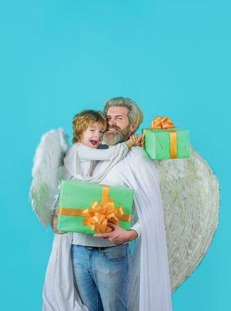Little cupid boy gives father gift. Father's day. Gift box. Happy father in angel costume with little son angel holds present. Cute angel. Valentines day. Father and son Angels. Christmas angels