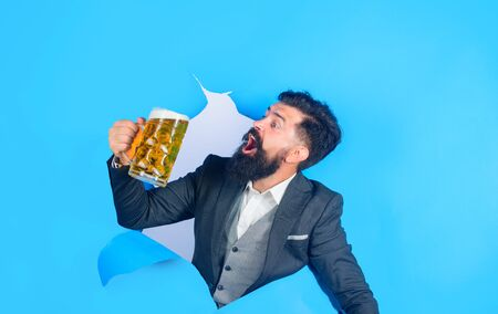 Drinks, alcohol, leisure, people concept. Satisfed man with beard holds mug of beer. Stylish man drinks beer. Lager and dark beer. Bearded man holds craft beer looking through paper hole. Oktoberfest