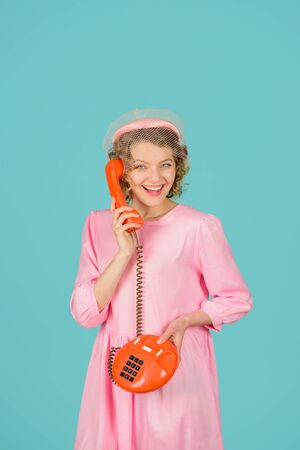 Smiling woman talking by retro phone. Girl holds handset. Landline phone. Communication. Woman with telephone handset. Phone communication