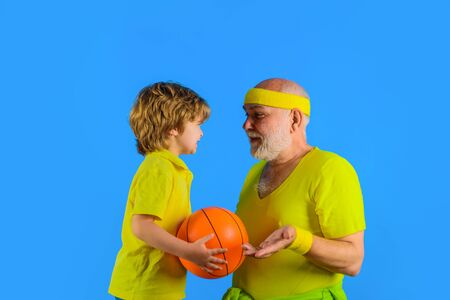 Grandfather teaching grandson to play basketball. Family time. Grandfather and kid playing. Family sport. Portrait of healthy grandfather and son workout. Sporting. Basketball. Sport game