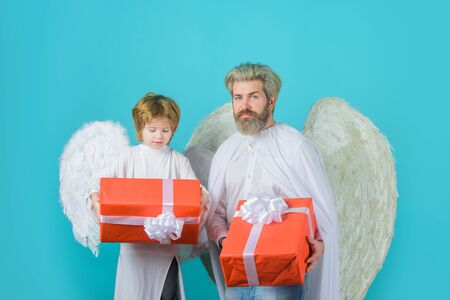 Gift box. Happy father in angel costume with little son angel holds present. Cute angel. Valentines day. Father and son Angels. Father's day. Little cupid boy gives father gift. Christmas angels Stock Photo