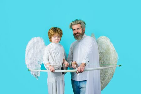 Father and son Angels. Father's day. Little cupid boy and father with bow and arrow. Happy father in angel costume with little son angel. Christmas angels. Cute angel. Gorgeous kid. Valentines day