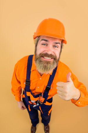 Repairman in full height. Business, building, industry, technology. Builder in hard hat. Engineers working. Advertising. Funny repairman. Thumbs up. Hard hat. Repairment tools Standard-Bild