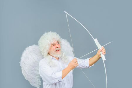 Love concept. Valentine angel. Handsome male angel Cupid. Bearded man with angel wings. Valentines day card. Valentines Day. Angel man with white wings. Cupid with bow and arrows. Valentines cupid 写真素材