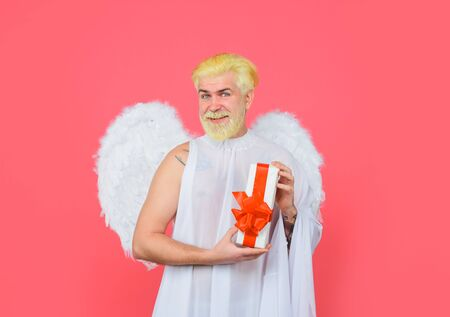 Cupid angel with present box. Love concept. February 14. Cupid with gift box. Valentine angel. Happy Valentines Day. Smiling man in angel costume. Valentines day angel. Cupid. Amour. Cupid with gift