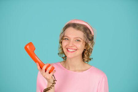 Woman talking on retro phone. Girl holds handset. Landline phone. Communication. Woman in pink dress with telephone handset. Phone communication