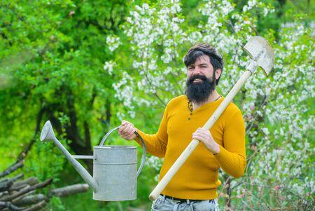 Smiling man preparing to planting. Plants. Watering. Gardening. Bearded gardener with garden watering can and spade. Work in garden. Gardener work. Farm. Farmer working in garden. Spring Zdjęcie Seryjne